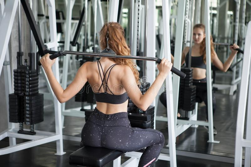 young fitness woman in sportswear exercising building muscles with machine Cable Crossover in sport gym . workout royalty free stock image