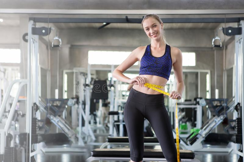 young fitness woman in sportswear measuring waist with a tape in sport gym royalty free stock photography