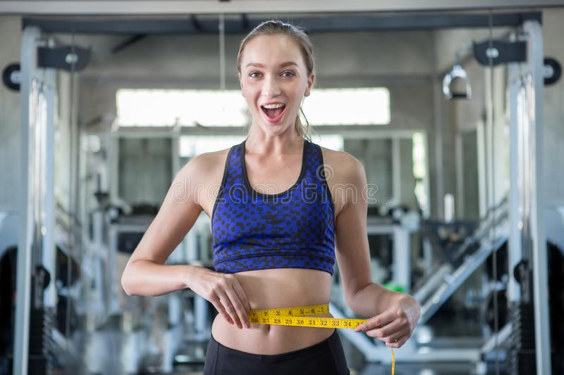 young fitness woman in sportswear measuring waist with a tape in sport gym stock photo