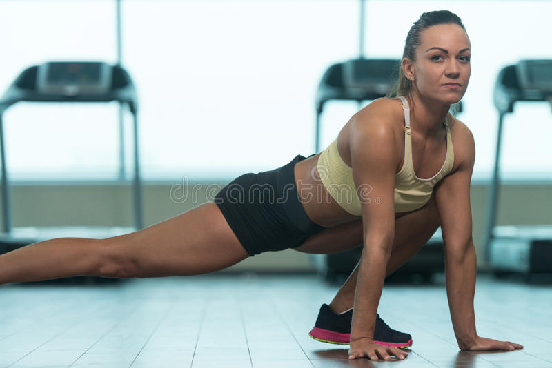 Young Fitness Woman Stretches At The Floor stock photos