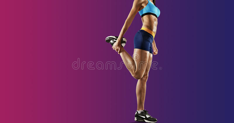Young fitness woman stretching legs. Isolated royalty free stock photography