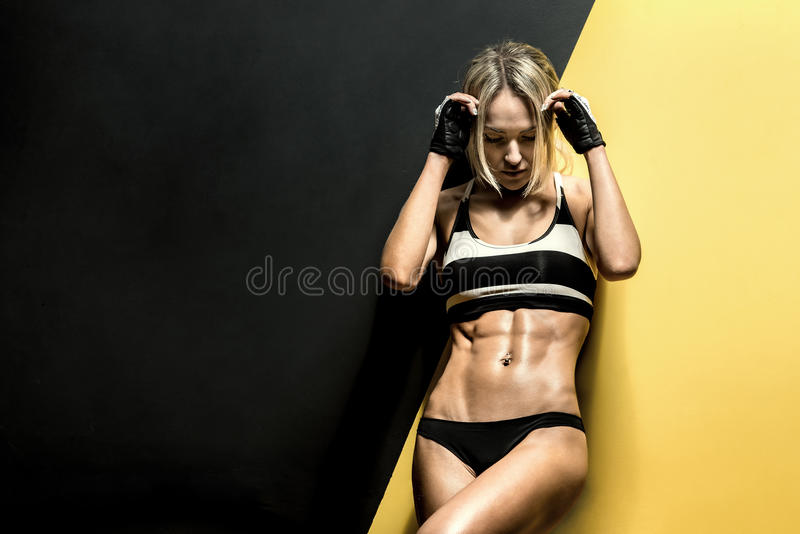 Young fitness woman. In swimsuit on black and yellow background, horizontal photo stock photography