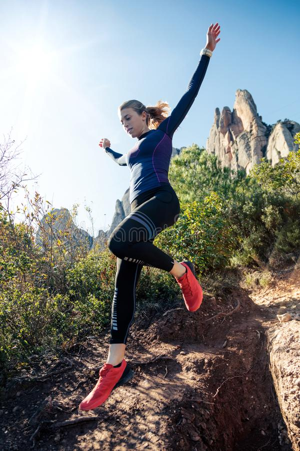 Young fitness woman trail runner running and jumping on rocky mountain stock image