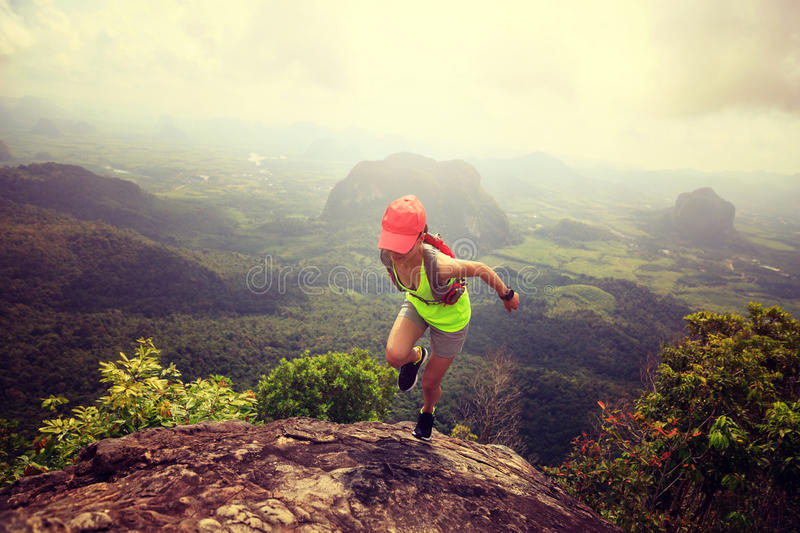 Woman trail runner running at mountain top stock photography