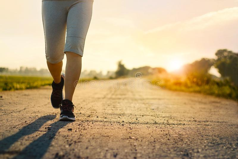 Young fitness woman trail running on rural road in summer royalty free stock photo