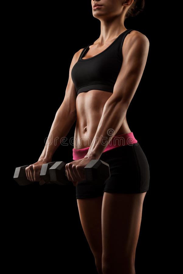 Young fitness woman in training pumping up muscles with dumbbell royalty free stock images