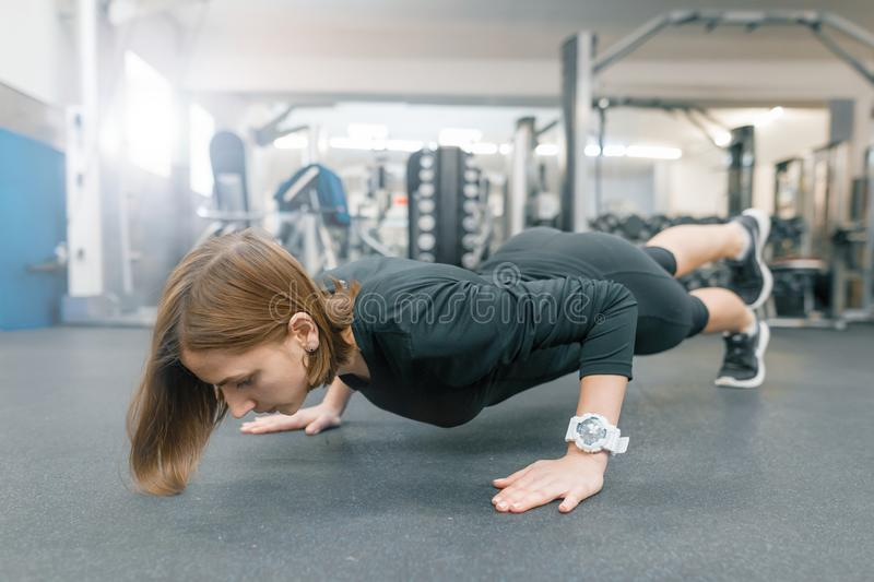 Young fitness woman working out doing push-ups on floor in sport gym. Sport, fitness, training, lifestyle and people concept royalty free stock images