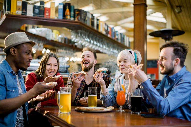 Young five people eating pizza and laughing while sitting in a fast food restaurant. Group of friends enjoying while stock photos