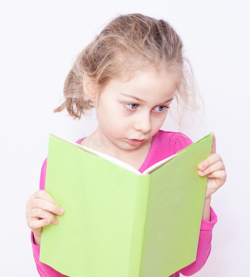 Young five years old child girl reading a book. Young five years old caucasian blond child girl reading green book on white background - childhood, education royalty free stock image