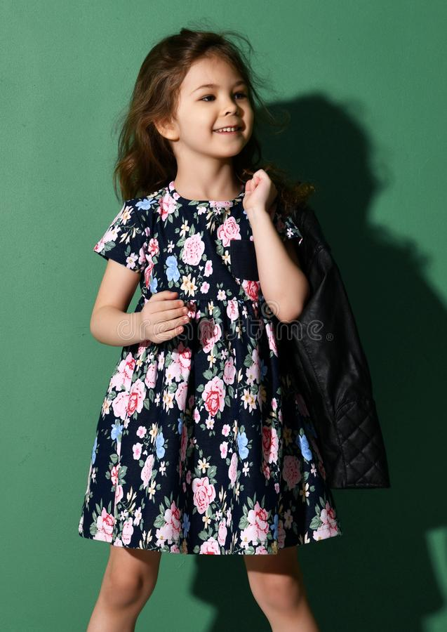 Young five years old girl kid posing in summer dress on green stock photo