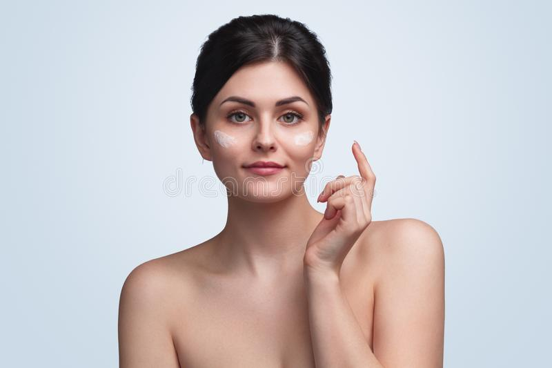 Tender brunette with cream on face stock images