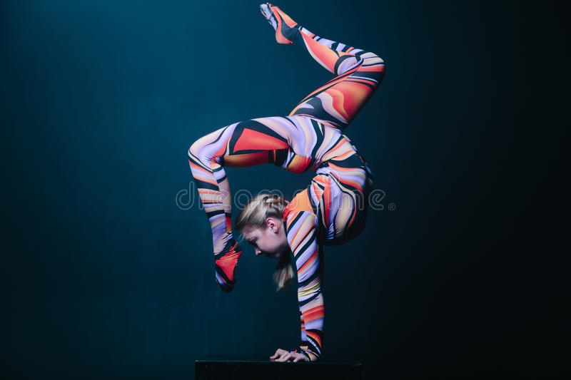 Young flexible blonde circus acrobat posing in studio in costume. Doing equilibre balance handstand on a cube. royalty free stock photography