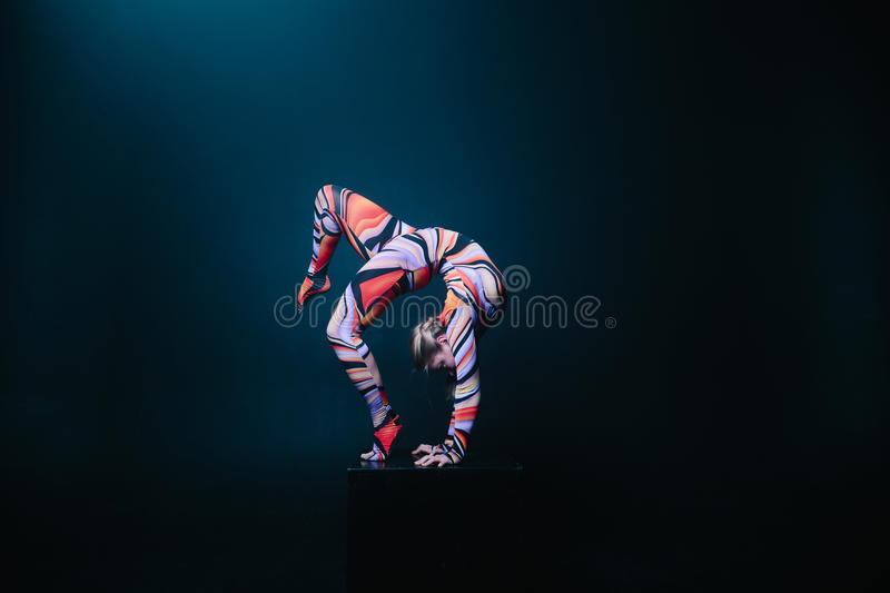 Young flexible blonde circus acrobat posing in studio in costume. Doing equilibre balance handstand on a cube. royalty free stock images