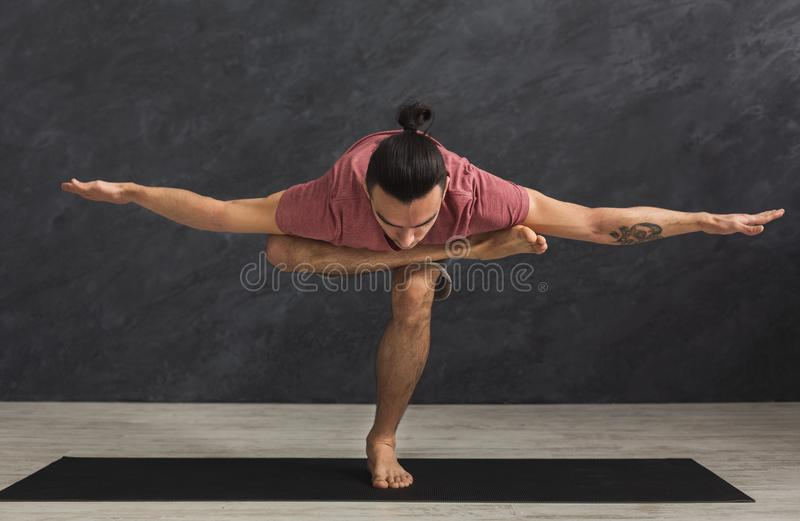 Young flexible man practicing yoga at gym royalty free stock photography
