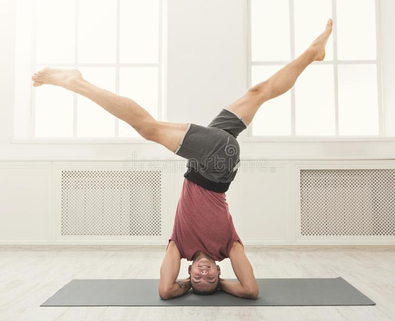Young flexible man standing on hands stock photo
