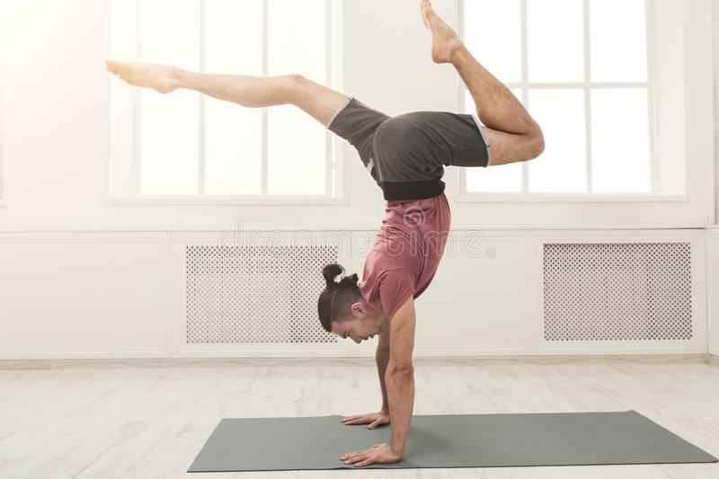 Young flexible man standing on hands royalty free stock image