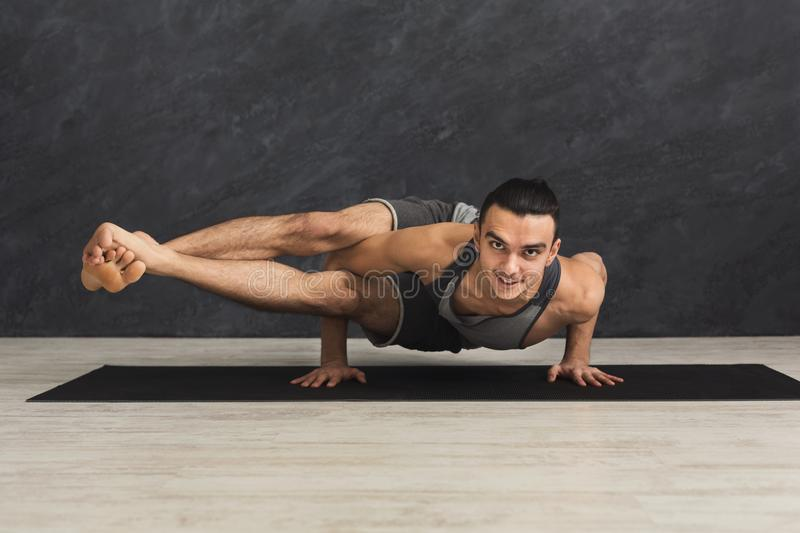 Young flexible man standing on hands stock photography