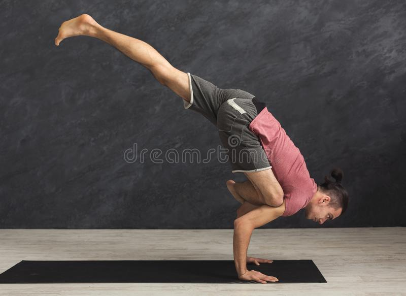 Young flexible man standing on hands royalty free stock photography