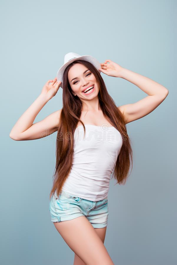 Young flirty brunette lady in summer outfit and hat is standing royalty free stock photos