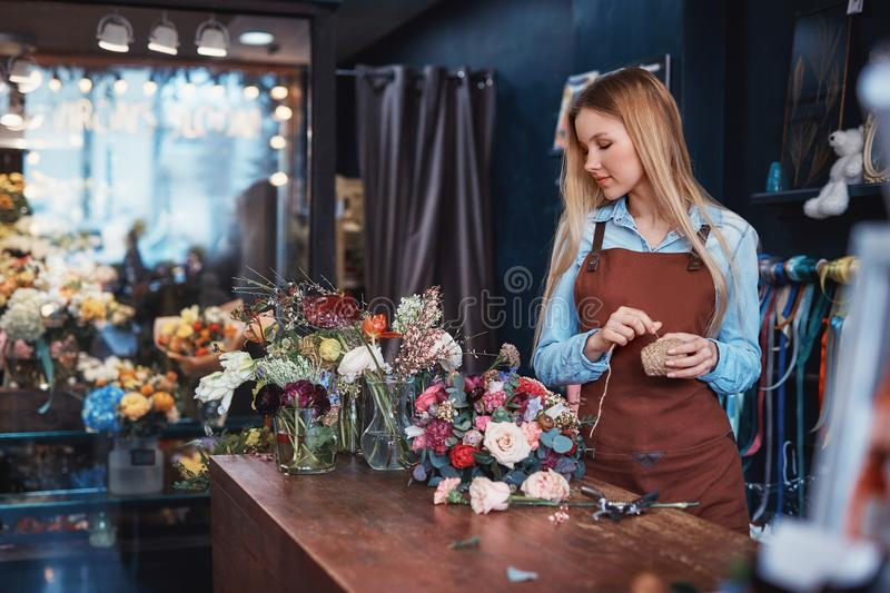 Young florist in an apron royalty free stock photography