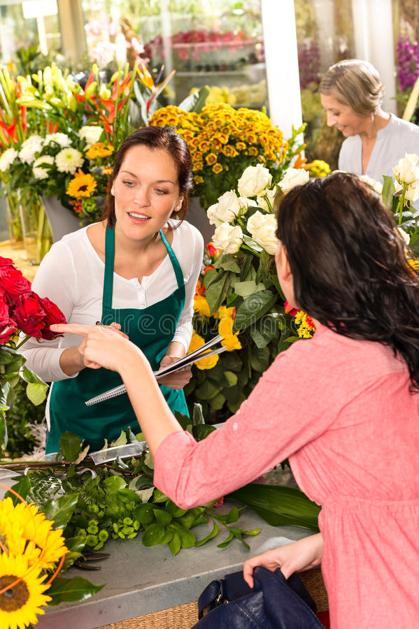 Young florist ordering roses woman customer flower. Young florist ordering roses women customer flower market retail shop royalty free stock images