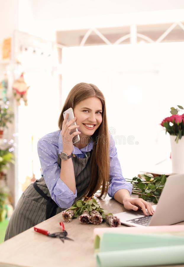 Young female florist working with laptop and talking on mobile phone in flower shop royalty free stock photo