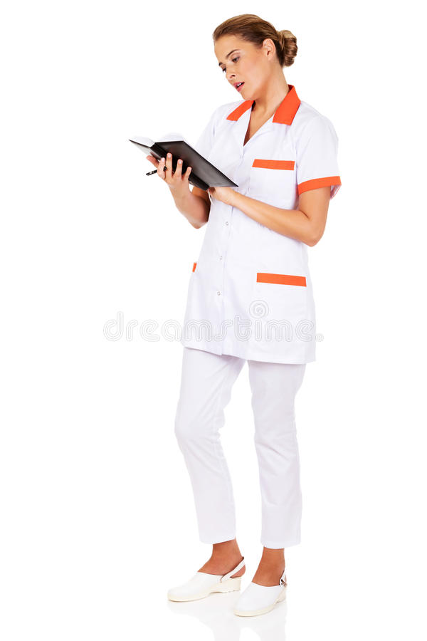 Young focus female doctor or nurse makes notes.  stock photo