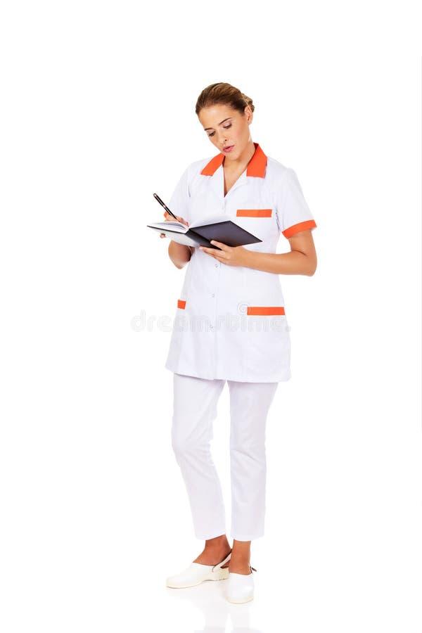 Young focus female doctor or nurse makes notes.  stock photos