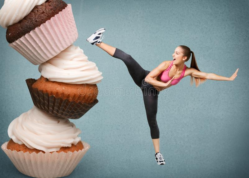 Fit young woman fighting off fast food royalty free stock image