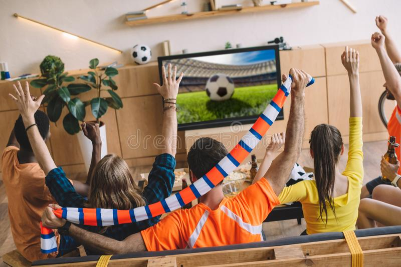 Young football fans celebrating and doing yes gestures while sitting on sofa during watch of soccer match. At home stock photo