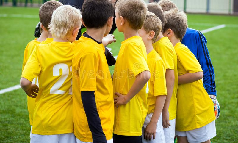 Young football soccer players with coach. Coach motivate children sports team royalty free stock images