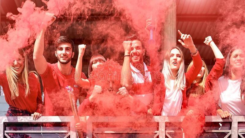 Young football supporter fans cheering at stadium with colored smoke stock photography