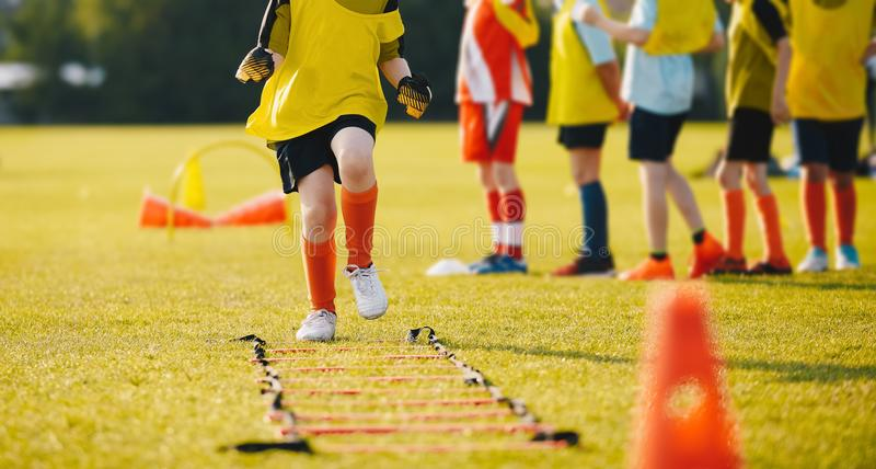 Young Footballer in Yellow Sportswear at Training Session on Grass Soccer Field. Young Athletes Training with Football Equipment. Football Speed Training for stock image