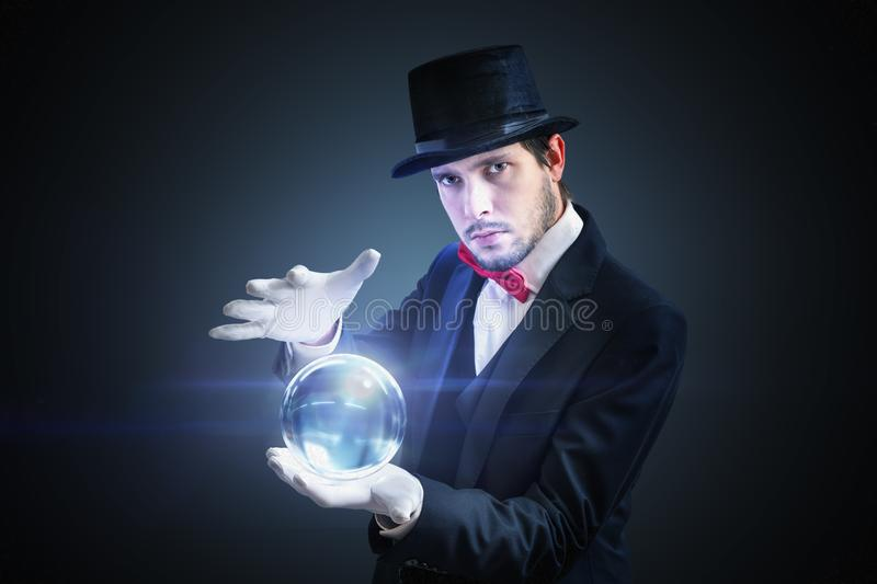 Young fortune teller is predicting future from magical crystal ball royalty free stock images