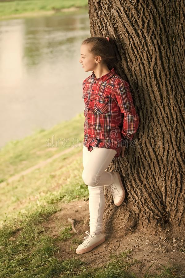 Young and free. Fashionable cute child on natural landscape. Adorable child with long blond hair in casual plaid style. Little child wearing fashion summer royalty free stock image