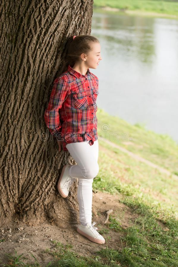 Young and free. Fashionable cute child on natural landscape. Adorable child with long blond hair in casual plaid style. Little child wearing fashion summer stock photography
