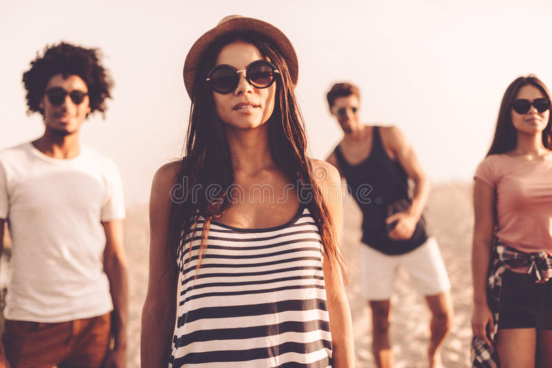 So young and so free. Four beautiful young people looking at camera while standing on the beach together stock images