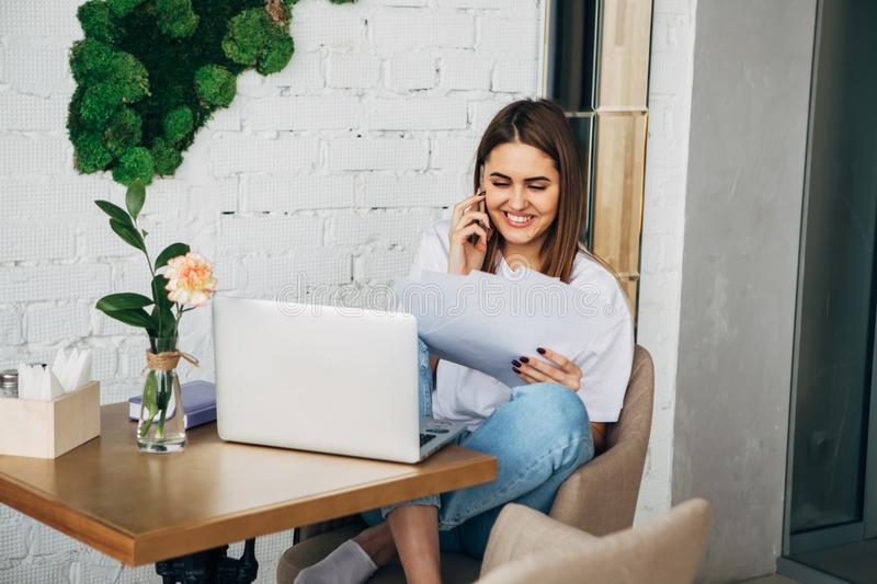 Young freelancer girl talking on the phone, holding a notebook, laptop on the table royalty free stock photos