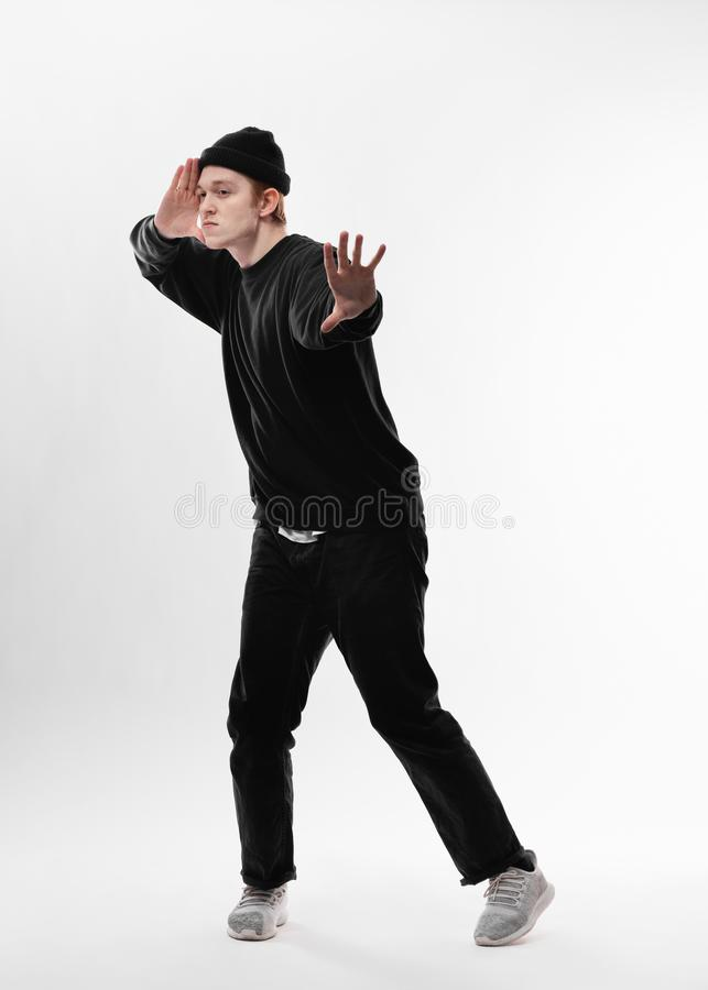 Young freestyle dancer dressed in black jeans, sweatshirt, hat and gray sneakers is dancing in the studio on the white royalty free stock images