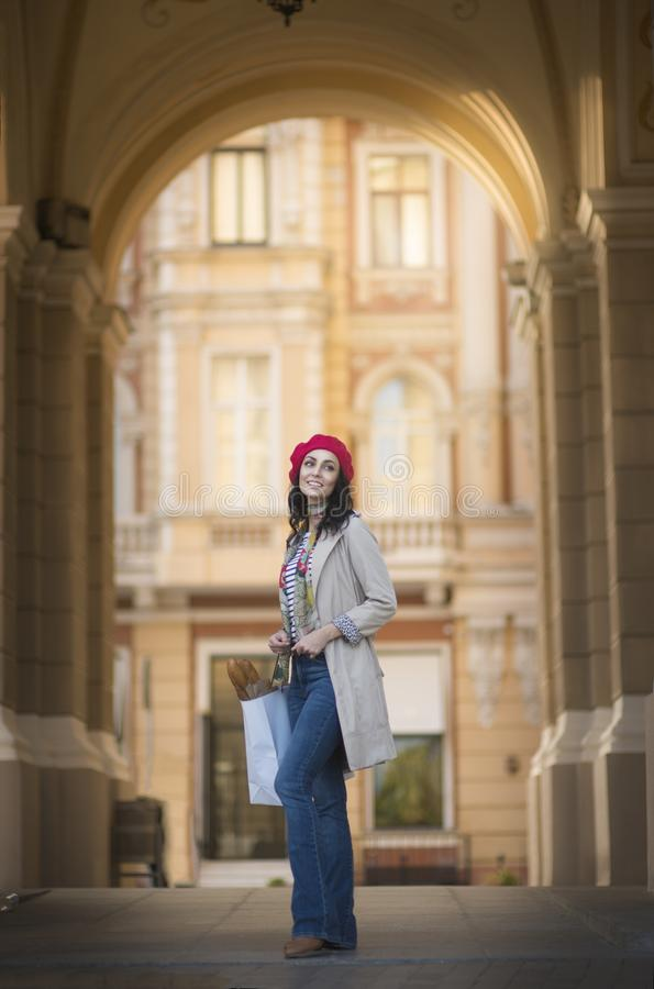 Beautiful brunette with french baguettes. Young French brunette woman in a red beret. Smiling and holding baguettes in her hands.nIn the historic part of the royalty free stock images