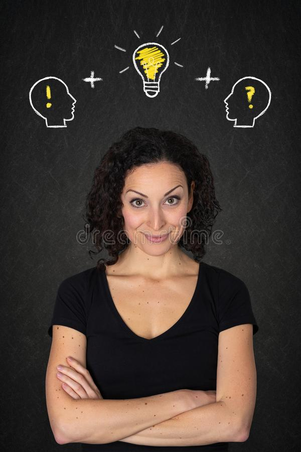Young woman with crossed arms, heads with ! and ? marks and light bulb idea on a blackboard background. royalty free stock images