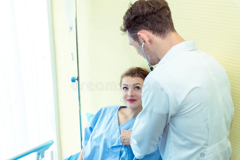 Young friendly caucasian pediatrician male doctor is examining patient woman on bed in hospital, consultation with stethoscope in stock image