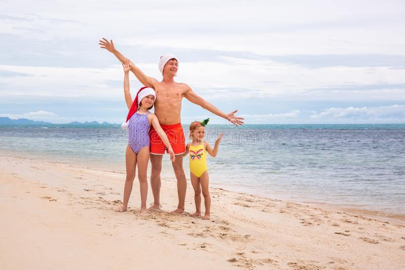 Young friendly family father and two dauthers are happy in summer Christmas on beach royalty free stock images