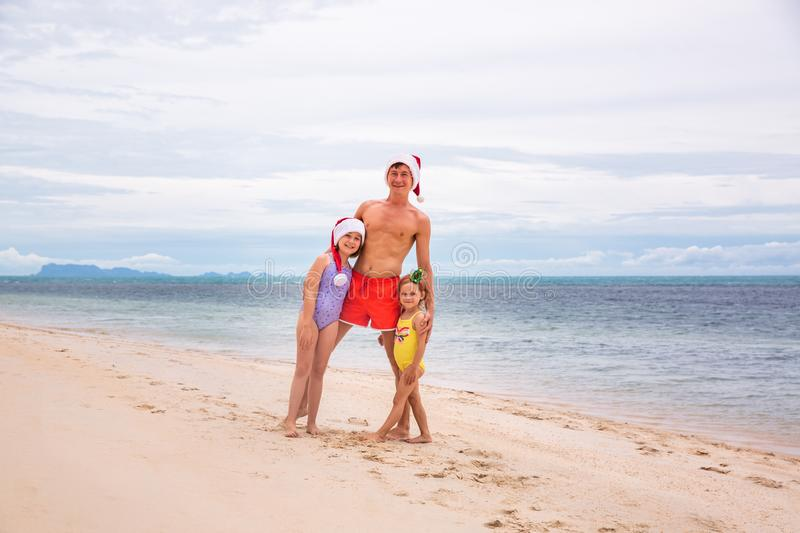Young friendly family father and two dauthers are happy in summer Christmas on beach royalty free stock photography