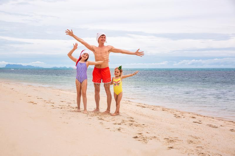 Young friendly family father and two dauthers are happy in summer Christmas on beach royalty free stock photo
