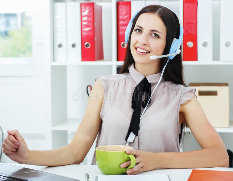 Young friendly latin woman with in business casual outfit using headset. stock photography