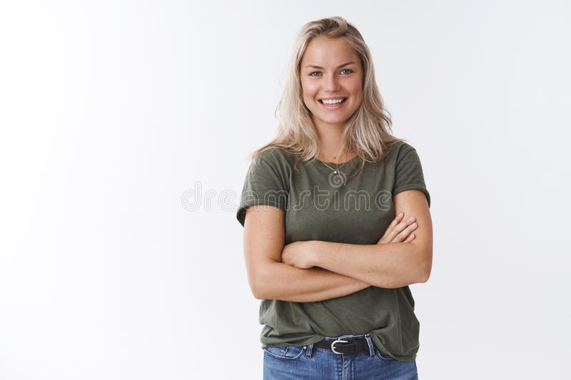 Young friendly-looking attractive mother talking other moms during b-day party crossing arms over body and smiling stock photo