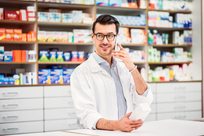 Young friendly male pharmacist with smartphone, making a phone call. royalty free stock image