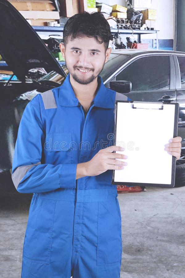 Young friendly mechanic holding clipboard with copy space. At a repair shop royalty free stock photo