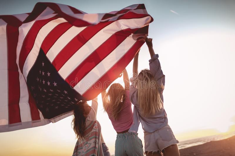 Friends carrying american flag on the beach stock image